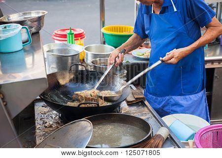 GEORGE TOWN MALAYSIA - MARCH 23: Chef cooks stir-fried noodles at Kimberly Street Food Night Market on March 23 2016 in George Town Malaysia.