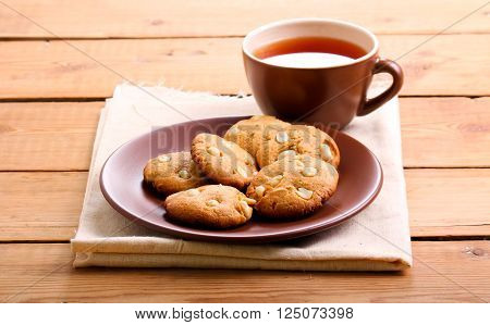 Peanut butter cookies with peanuts and cup of tea