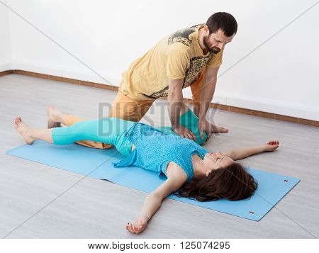 Pair exercises. Man performing thai massage stretching woman's legs woman is laying on the mat relaxing
