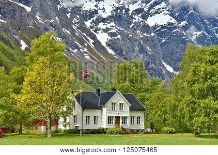 Romsdalen Norway - June 1 2015: Wooden country house in front of a massive mountainscape in Romsdalen valley Norway