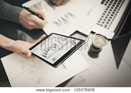 Research department working process.Photo female hands holding modern tablet with analitical info screen. Man holding pen for signs documents. Discussion startup idea.