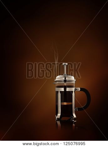 close up view of  french-press filled with fresh black coffee   on brown background