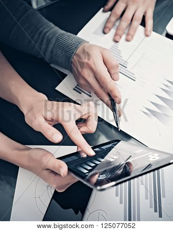 Research department working process.Photo woman showing business reports modern tablet. Statistics graphics screen.Banker holding pen for signs documents, discussion startup idea. Vertical