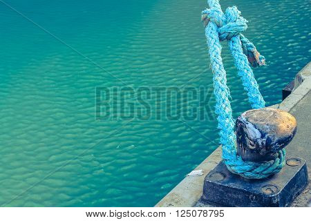 Dock with blue rope in harbor with turquoise water background.
