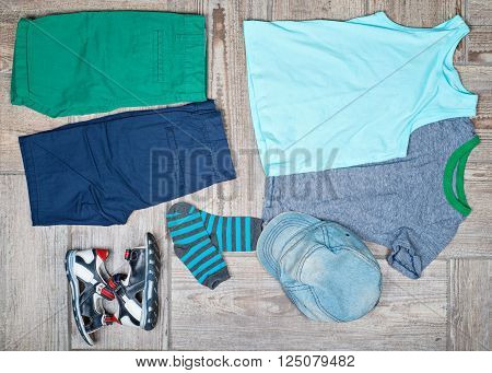 Flat lay photography of kid's casual outfits. Boy's casual outfits on wood board background