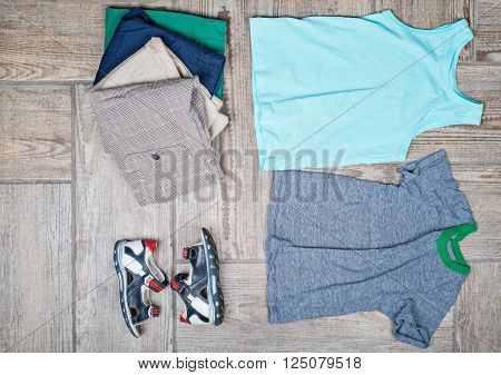 Flat lay photography of some boy's casual outfits. Boy's casual outfits on wood board background