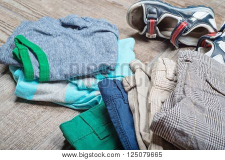 Some boy's casual outfits in stack. Boy's casual outfits on wood board background