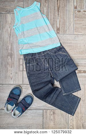 Flat lay photo of boy's clothing on the floor. Boy's casual outfit on wooden background