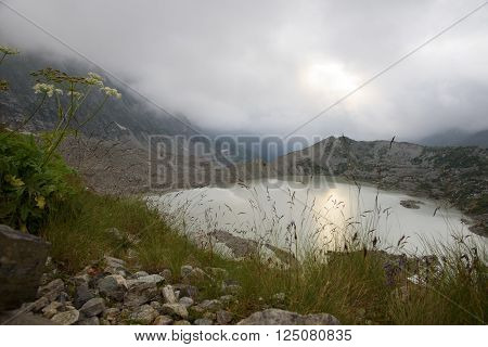 glacial lake and moraines on the background of cloudy mountains