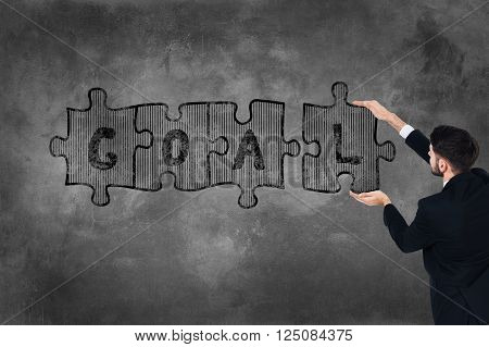 Achieve your goal! Rear view of young man in full suit touching concrete wall with illustrated puzzle on it