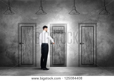 Choosing success. Rear view of young man in formalwear openning an illustrated door on the concrete wall