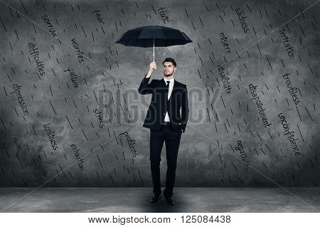 Feeling protected. Full length of confident young man in full suit holding umbrells while standing in front of the concrete wall