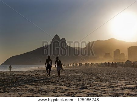 RIO DE JANEIRO, BRAZIL - APRIL 8: Silhouette of local surfers walking on the sand of Ipanema beach in the afternoon April 8, 2016 in Rio de Janeiro, Brazil.