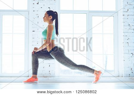 Warming up before training. Side view of young beautiful young woman in sportswear doing stretching while standing in front of window at gym
