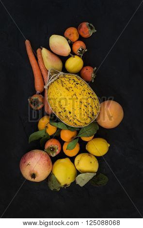 Mixed yellow and orange fruit and veggies assortment, ingredients for smoothie. Melon, garnet, grapefruit, carrot, persimmon, lemon, quince, pear over black slate stone background, top view
