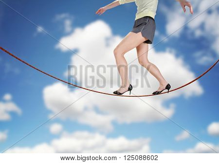 a woman walking on a tightrope made of string for the concept of risk or danger in the business corporate world isolated on a cloudy sky background