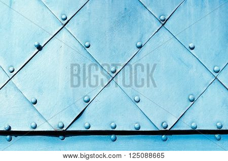 Metal rough background. Light blue textured metallic surface of aged carved metal plates with small rivets on them.