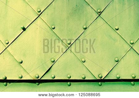 Metallic background - dirty yellow textured steel superficies of old carved metal plates with small rivets above