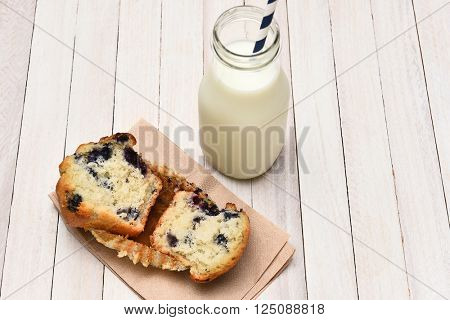 High angle view of a blueberry muffin and bottle of milk on a rustic white table. The muffin is broken in half on a napkin.