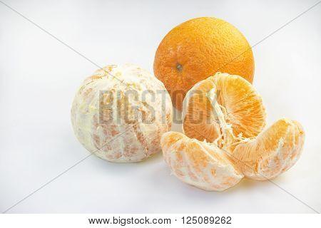 Three orange fruits on a white background