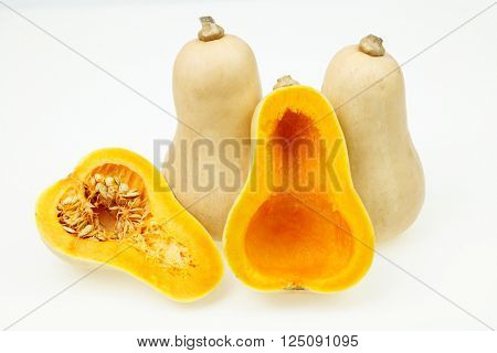 Butternut squash fruits, one cut in half, on white background.