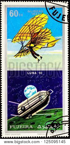 MOSCOW, RUSSIA - APRIL 09, 2016: A stamp printed in Fujeira shows spacecraft Luna 10 and ancient glider (1852), series