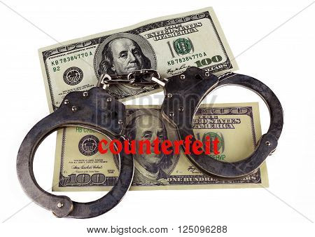police handcuffs false and real hundred-dollar bill. the concept of counterfeiting of money and punishment.