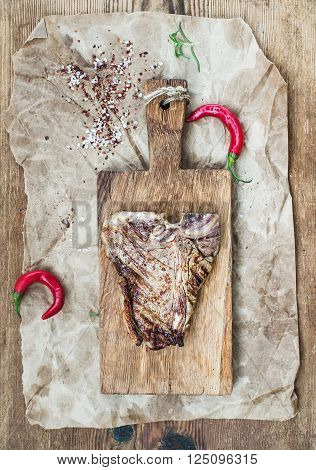 Cooked beef meat t-bone steak on serving board with red chili peppers, spices, fresh rosemary over oily craft paper and rustic wooden background, top view