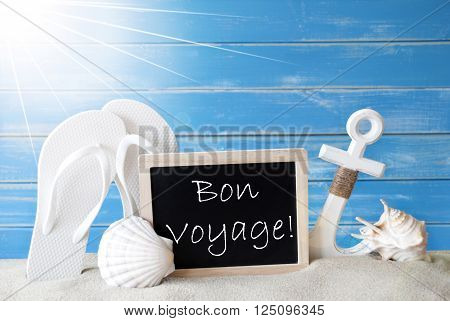 Chalkboard With French Text Bon Voyage Means Good Trip. Blue Wooden Background. Sunny Summer Card With Holiday Greetings. Beach Vacation Symbolized By Sand, Flip Flops, Anchor And Shell.