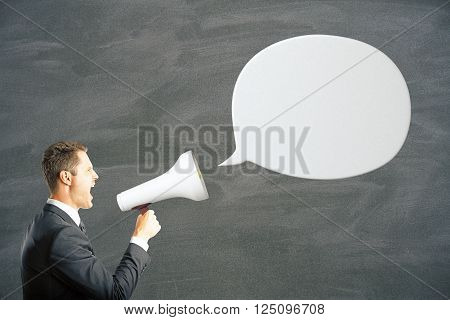 White speech bubble and caucasian businessman shouting into megaphone. Mock up