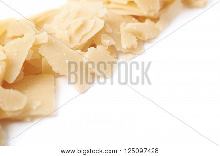 Line of parmesan cheese flakes isolated over the white background, close-up crop fragment as a copyspace shallow depth of field backdrop composition