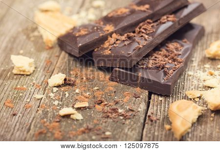 Pieces of chocolate and chocolate crumbs on old boards. Rural style close up small depth of sharpness ** Note: Shallow depth of field