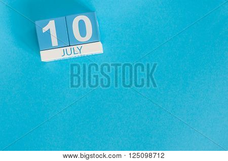 July 10th. Image of july 10 wooden color calendar on blue background. Summer day. Empty space for text.