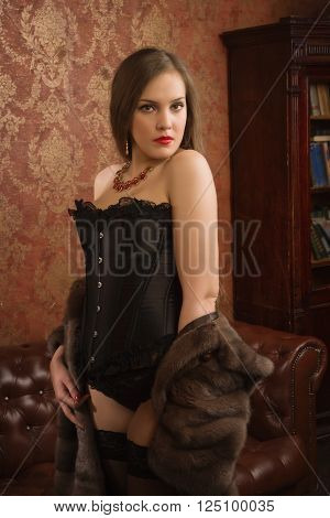 Beautiful and sexy brunette young woman wearing black lingerie fur cape and stockings at vintage interior