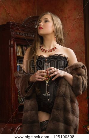 Beautiful and sexy brunette young woman wearing black lingerie fur cape and stockings with a glass of champagne