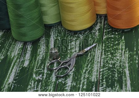 Macro photo of scissors and thimble on a background thread on a wooden background vintage green table