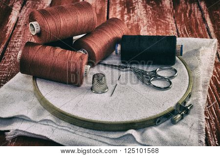 Vintage photos of items for sewing and embroidery on the background of a wooden table