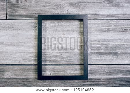 Blank see-through frame on antique wooden surface. Mock up
