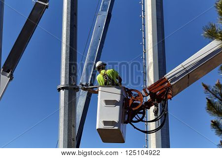 Utility workers in a boom crane basket servicing utility poles