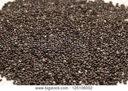 a heap of  chia seeds rich in omega-3 fatty acids, on white background