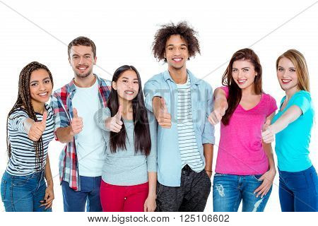 Studio shot of nice young multicultural friends. Beautiful people showing thumbs up, looking at camera and cheerfully smiling. Isolated background
