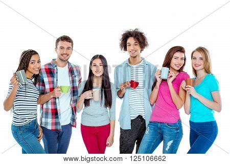 Studio shot of nice young multicultural friends. Beautiful people with cups of coffee looking at camera and smiling. Isolated background
