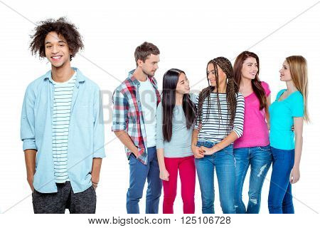 Studio shot of nice young multicultural friends. Beautiful people chatting. Focus on african boy. He looking at camera and smiling. Isolated background