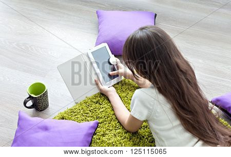 Reading e-books.  little girl reading e-book while lying on the floor. Education, leisure, technology and the concept of the Internet - a little girl with a tablet PC at home.