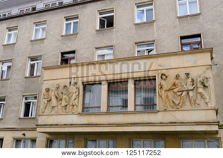 BRATISLAVA, SLOVAKIA - JULY 7, 2009: Communist era relief of architects planning on the left and workers toiling on the right, on a building facade at Ursulinska street