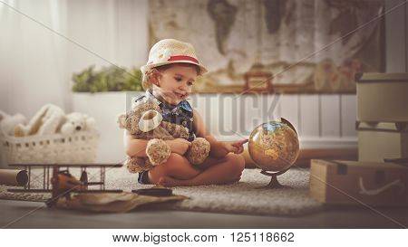 Concept travel. child girl at home dreaming of travel and tourism exploring the world map and globe