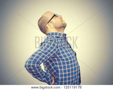Caucasian man in blue shirt struggles with intense back pain on gray background.