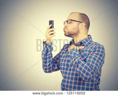 Caucasian man doing a selfie with a kiss. Isolated on a gray background.