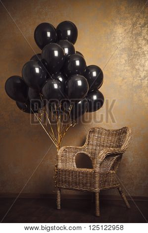 Bunch Of Black Balloons And Chair On Gold Background