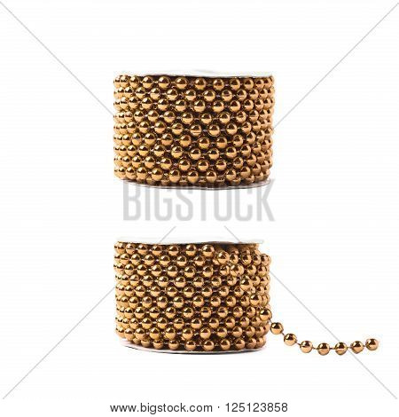 Small golden beads garland thread on a reel isolated over the white background, set of two different foreshortenings
